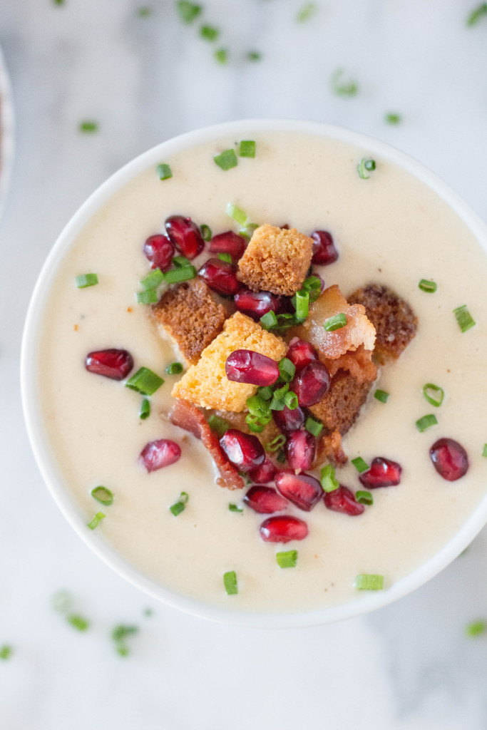 Creamy Parsnip Soup with Cornbread Croutons, Crispy Bacon, & Pomegranate Arils! It's perfect for serving buffet style at a holiday party! It's all about those toppings!   yestoyolks.com