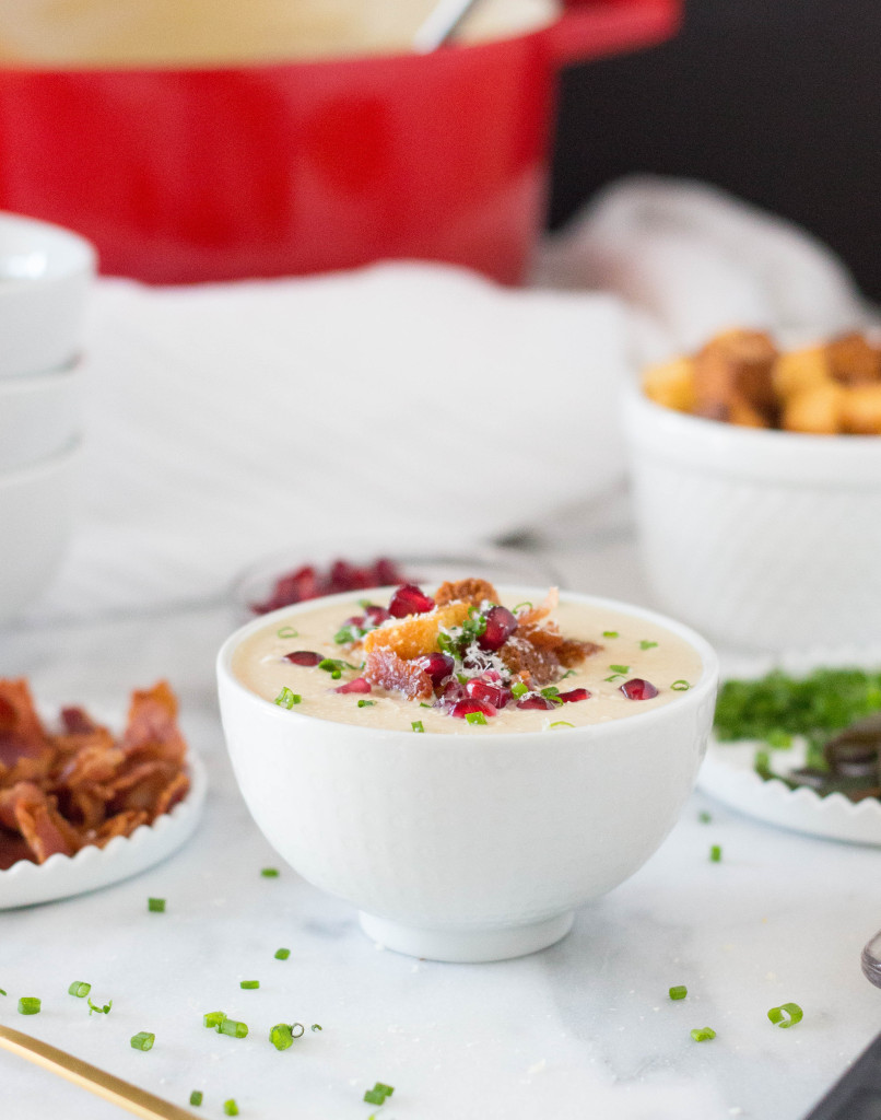 Creamy Parsnip Soup with Cornbread Croutons, Crispy Bacon, & Pomegranate Arils! It's perfect for serving buffet style at a holiday party! It's all about those toppings! | yestoyolks.com